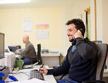 Hipster clerk smiling at phone in real old office